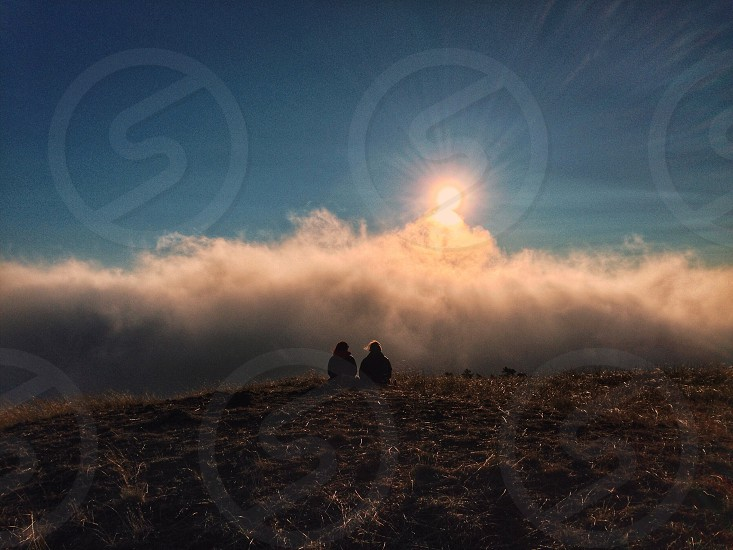 2 people sitting on ground watching sunrise photo