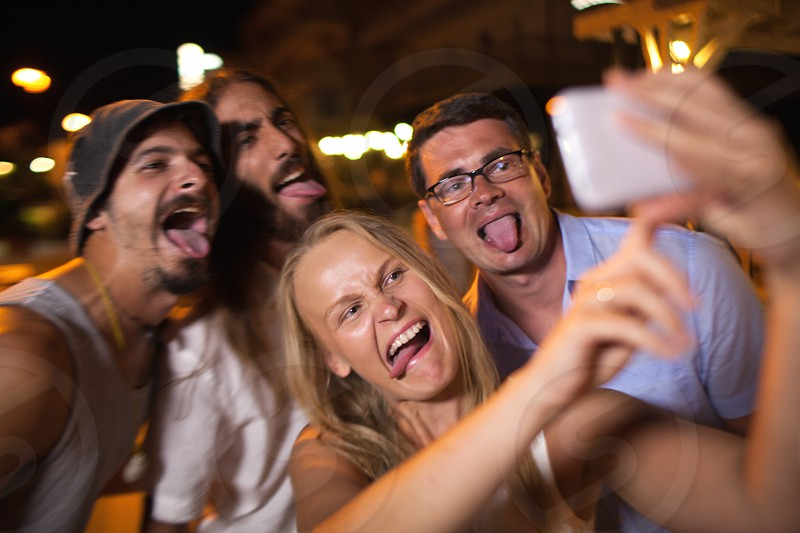 Young friends with funny faces making smart phone selfie at night. They fooling and putting out tongues photo