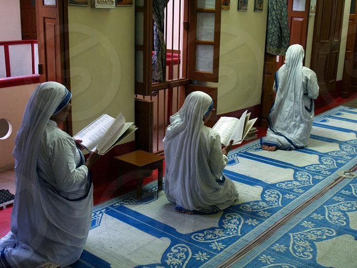 Nuns kneeling in prayer at Mother Tereasa's Hospice in Varanasi India       photo