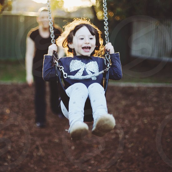 girl in blue jacket swinging photo