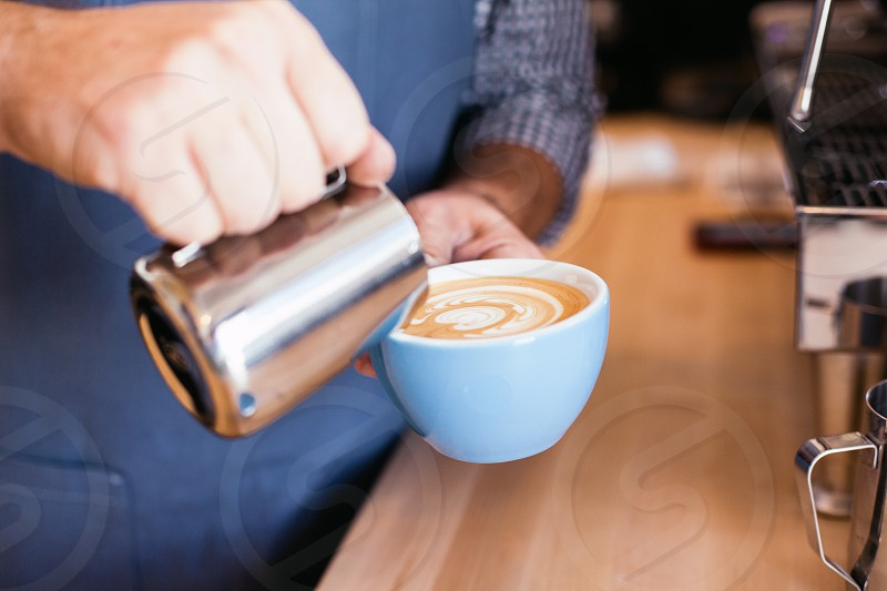 latte pouring of white tea cup photo