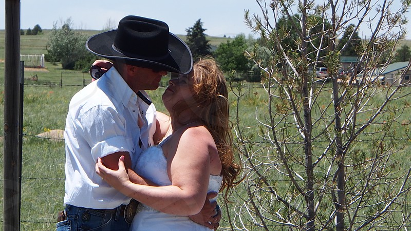 man wearing white shirt and black cowboy hat about to kiss a woman wearing white tops beside tree photo