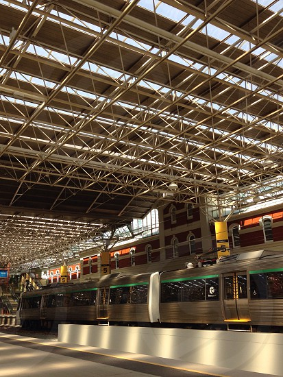 photo of green train below white and gray metal roof photo