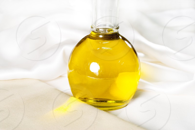 italian exta virgin olive oil over a white silk background photo