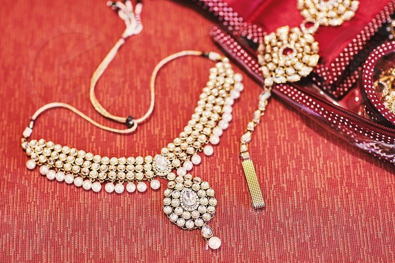 Glitter necklaces with pearl decoration of indian bride on red velvet background photo