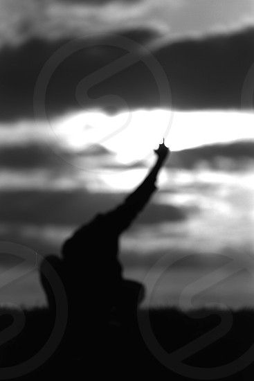 Silhouette of a man kneeling down with one arm high up in the air making a victory sign gesture photo