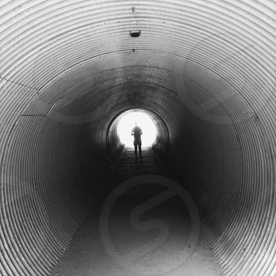person standing inside the tunnel photo