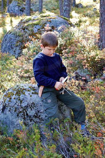 boy in black long sleeved shirt sitting on stone photo