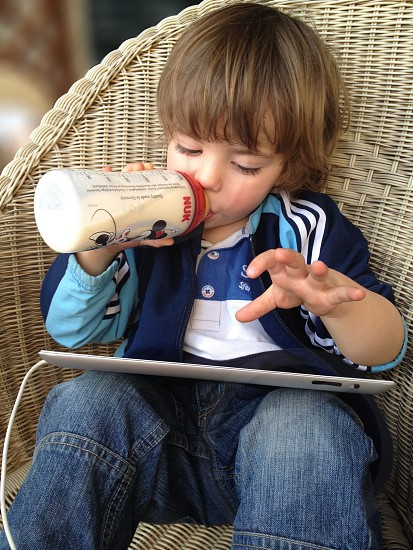 toddler in striped jacket and jeans drinking bottle on ipad photo