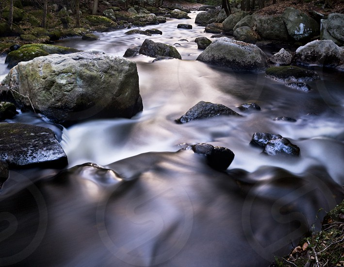 water flowing over gray stones photo