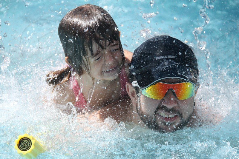 man wearing sunglasses and black cap swimming in swimming pool with girl riding his back photo