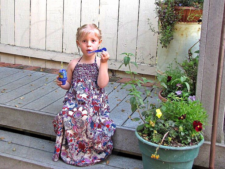 girl wearing red white and blue floral halter neck dress playing bubble sitting on wooden stairs photo