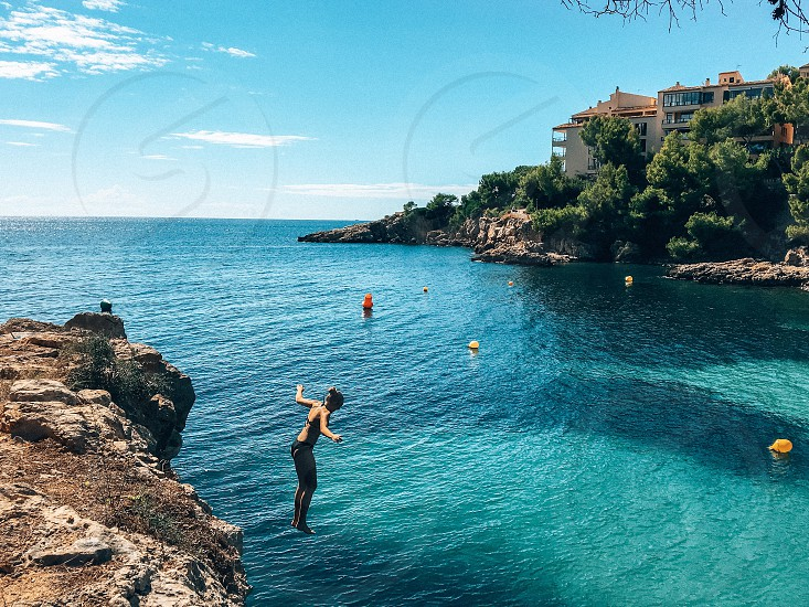 Girl jumping into the sea from the rock  photo