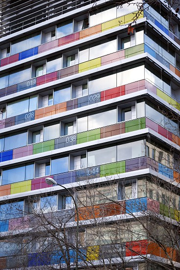 Bottom view of a modern building with colored and numbered glass balconies. photo
