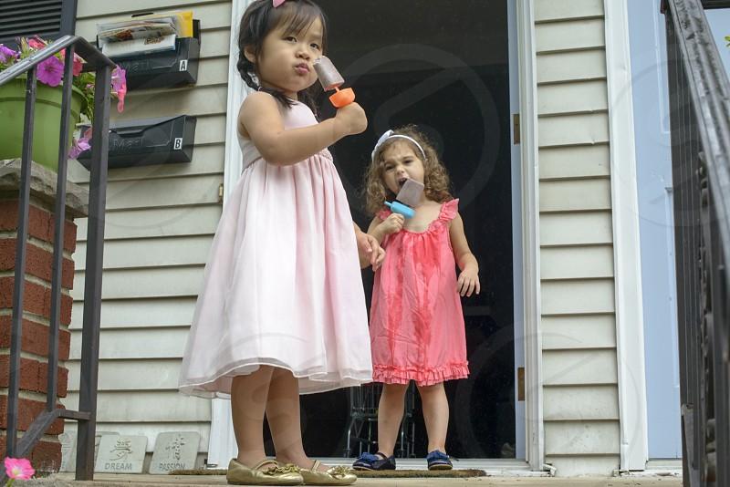 2 girls eating popsicles at the veranda photo