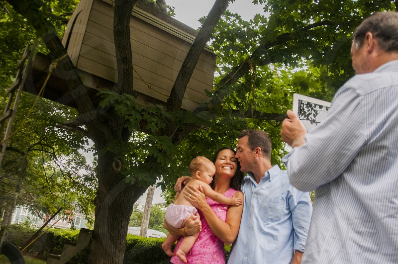 man kissing woman carrying topless baby near tree house photo
