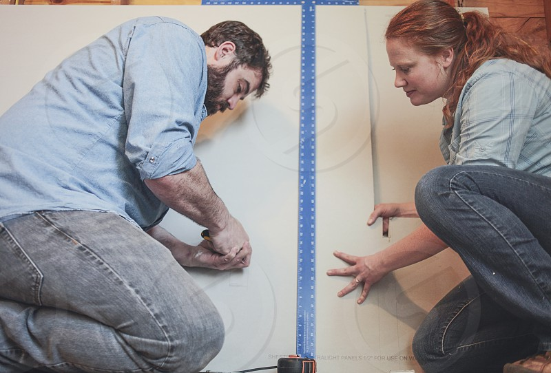 A man and woman work together on a construction project.  photo