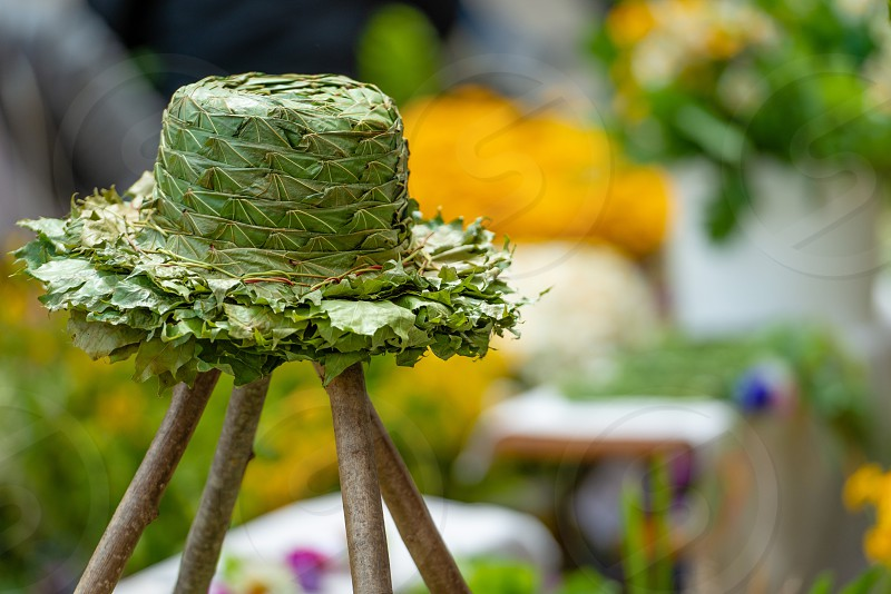 Wooden stand with a hat made of green wooden leaves. photo