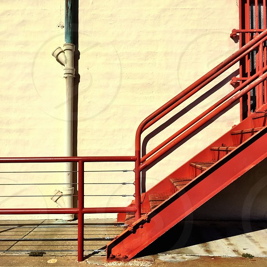 Red metal staircase against yellow wall.  photo