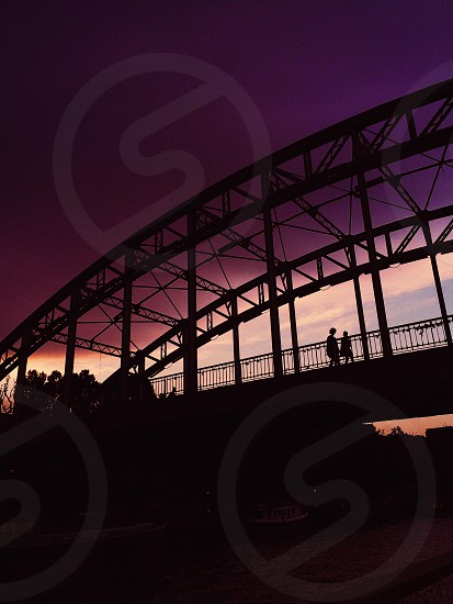 2 man silhouettes walking on the bridge photo