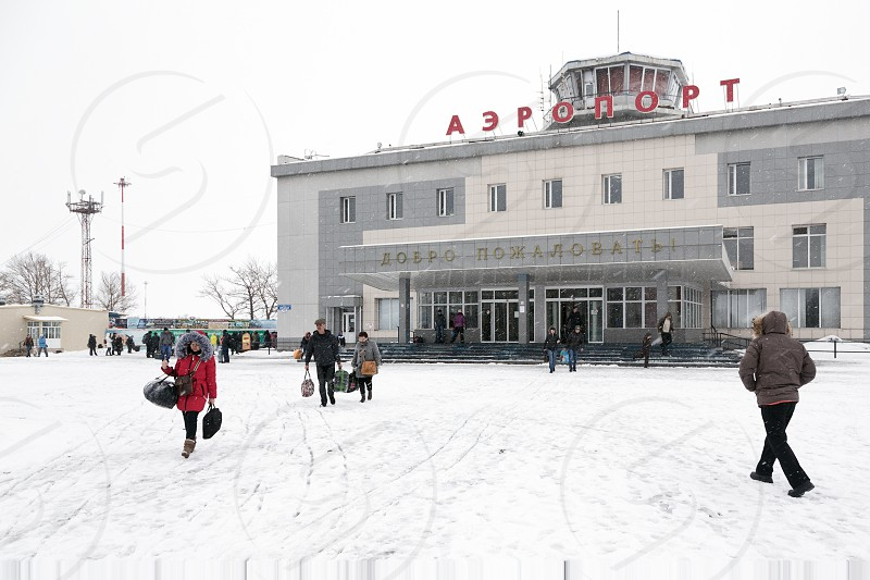 PETROPAVLOVSK-KAMCHATSKY KAMCHATKA RUSSIA - MARCH 19 2015: Winter view of the airport terminal Petropavlovsk-Kamchatsky (Yelizovo airport) and the station square with the passengers. photo