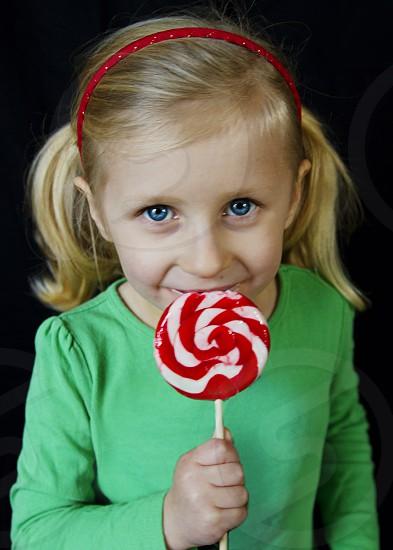 girl holding twirl lollipop  photo