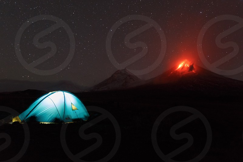 Volcanic landscape of Kamchatka Peninsula: view of illuminated tourist tent at night on background erupting active Klyuchevskoy Volcano. Russian Far East Kamchatka Klyuchevskaya Group of Volcanoes. photo