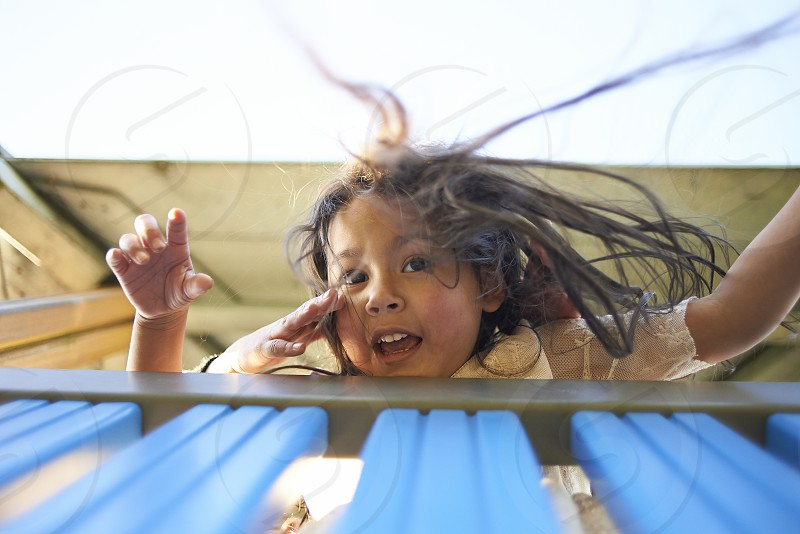 Young Asian girl on top of a watchtower at a playground looking down with her hair going wild and an excited expression on her face photo