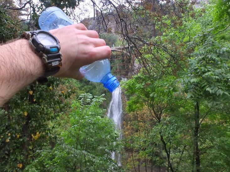 person holding blue plastic bottle photo