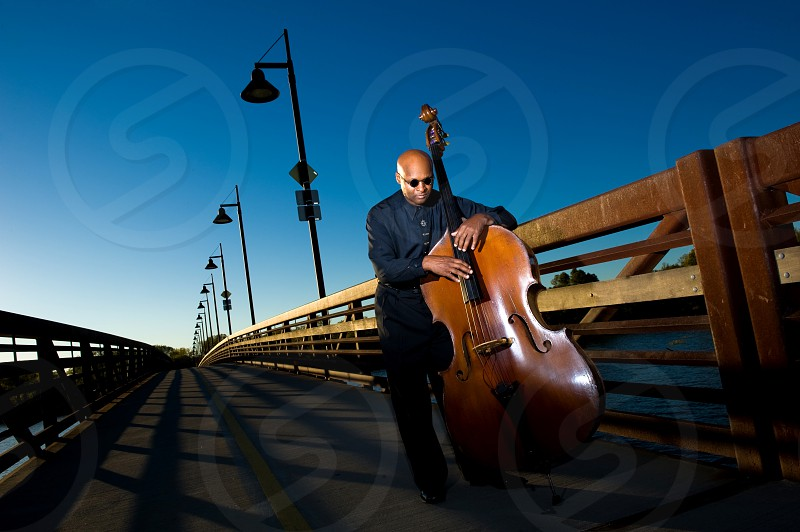 Image of a bass player on a bridge at dusk photo