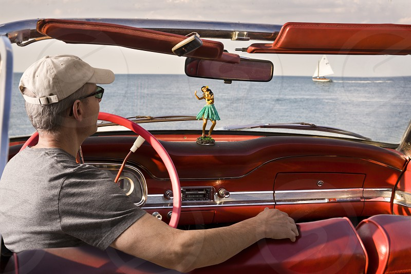 man in gray shirt wearing black framed sunglasses and beige baseball cap in red convertible car near body of water during daytime photo