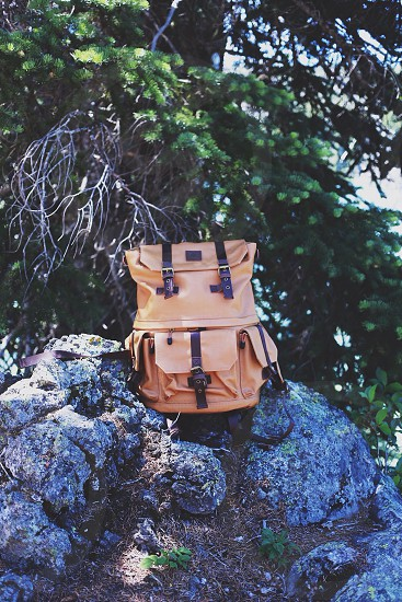 brown leather backpack on a rock photo