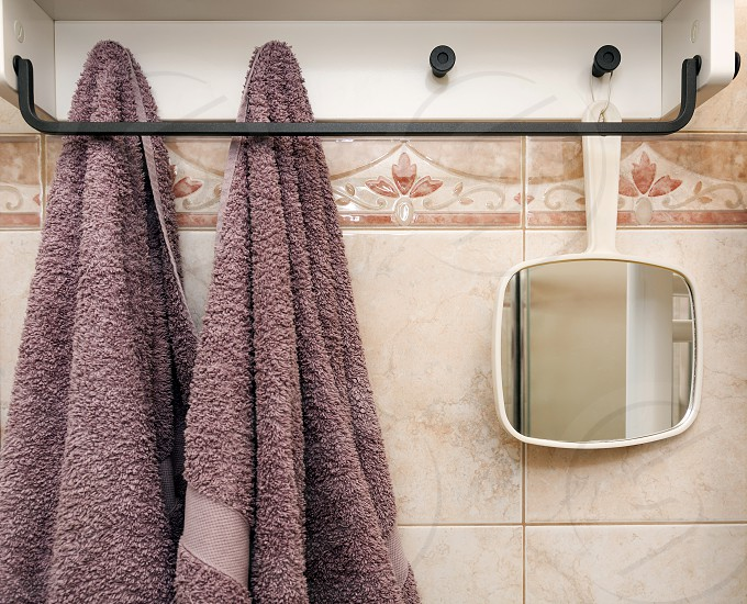 hanging objects in the tiled bathroom: two towels and a white mirror photo