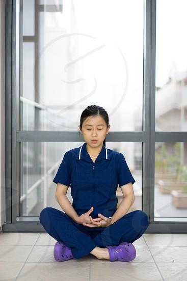 Nurse meditating on hallway photo