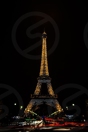Eiffel Tower Paris France. Long exposure capturing the light trails of the busy traffic flow. photo