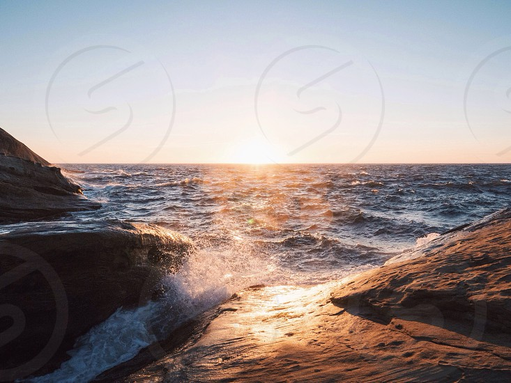 sea waves crushing down on rock formations photo