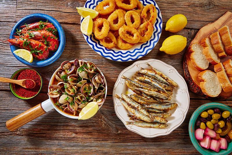 Tapas mix spanish clams olives shrimps calamari romana and fried anchovies fish photo