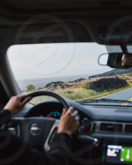man sitting on driver seat holding nissan steering wheel photo
