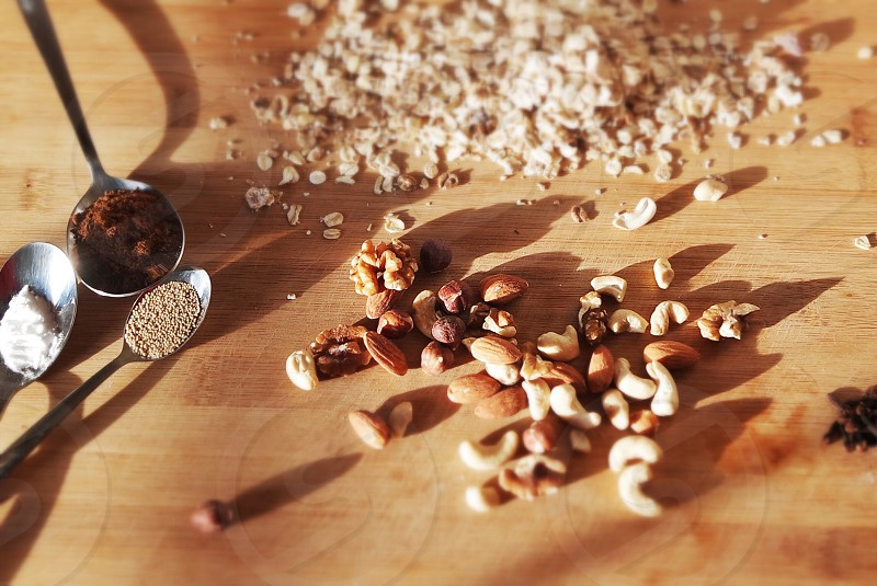 Whole foods mixed nuts and oats displayed on a wooden chopping board photo
