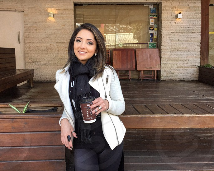 woman with brown long hair in black sweat shirt wearing white jacket holding brown coffee cup during daytime photo