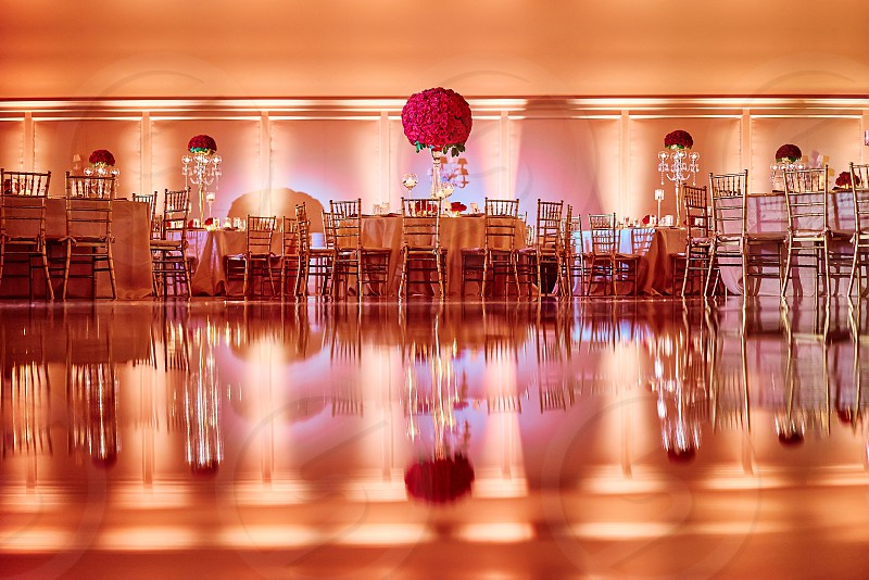 The luxury indian wedding reception dinner venue for sangeet night decoration with red roses and gold theme The dinner table reflection on the party dance floor photo