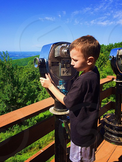boy in black t shirt using blue and grey coin operated binoculars photo