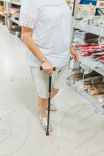 Elderly woman walking with her cane and shopping photo