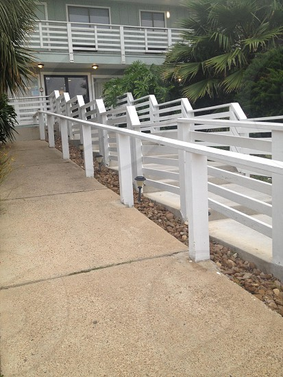 grey concrete pathway and white wooden railings photo