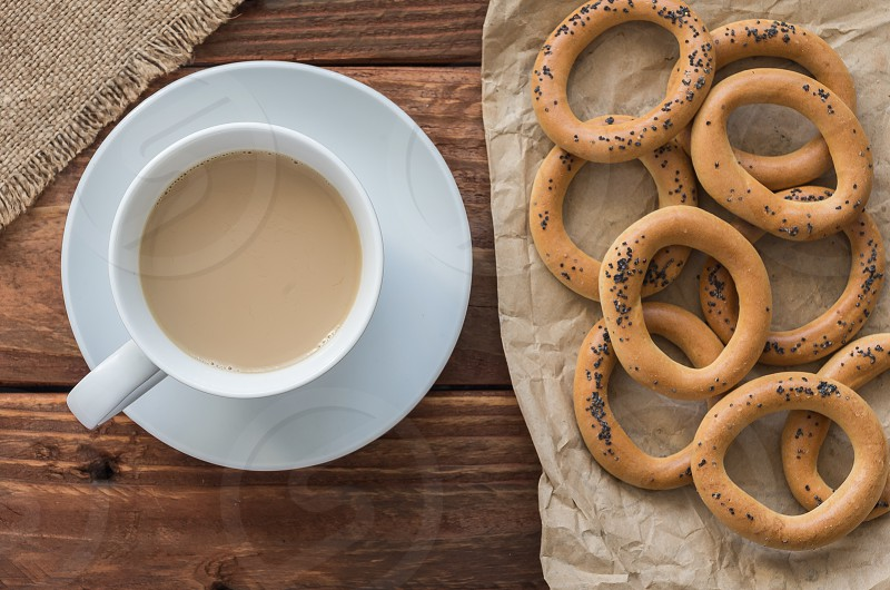 bagel breakfast brown cinnamon coffee cup drink eat feed flour food kitchen milk paper porcelain sackcloth saucer snack table white wooden wrapping wrapping-paper photo