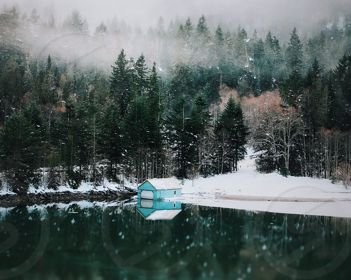 blue boathouse on a lake surrounded by pine tree covered snow hills photo