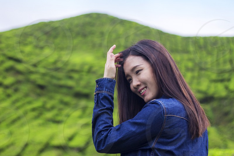 Asian woman laughing happily with tea plantation nature scenery as background photo