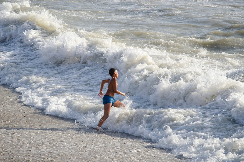 person in blue boxer shorts running on seashore photo