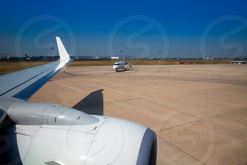 Airplane wing in airport with aircraft background with blue sky photo