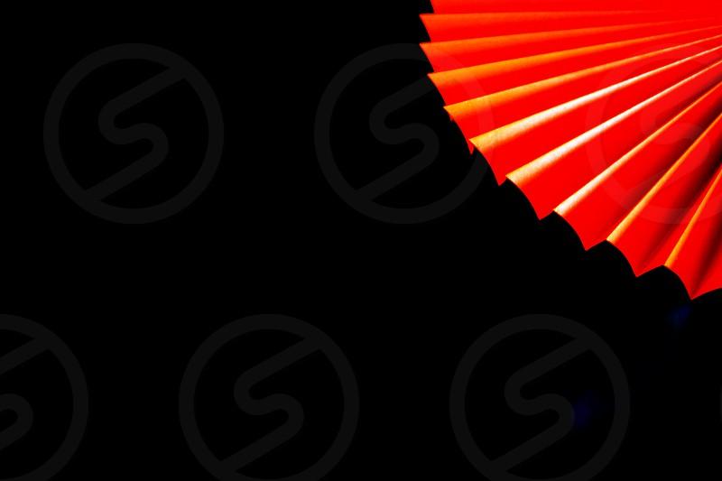 Folded  orange fan is in one corner of a black background. photo